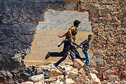 Member of the Free Syrian Army are seen rushing to take cover in Anadan following a government airstrike. The city resembled a ghost town on Monday, June 25, 2012. It bears the scars from Syrian President Bashar al-Assad's use of military force to crush an opposition movement that has spawned an armed insurgency against his rule. (Photo by Vudi Xhymshiti)