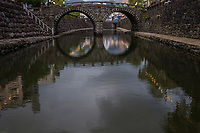 """Megane Bridge - Meganebashi or Spectacles Bridge, over the Nakashima River was built in Nagasaki in 1634.  Said to be the oldest stone arch bridge in Japan and has been designated as an Important Cultural Property of Japan. It received the nickname """"Spectacles Bridge"""" because its two arches and their reflection in the water create the image of a pair of spectacles."""