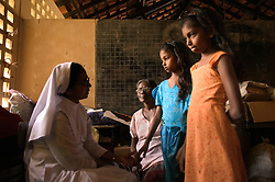 Sister Rita Sebastian comforts sisters Brianna and Shrianna Barthelot, 13 and 11, who lost both parents and their older brother in the tsunami, Batticaloa, Sri Lanka, March 7, 2005. They are now living with relatives at night and spending most of their days at the convent where the rest of their village is staying. Residents of the small Christian village Dutch Bar spent more than six weeks in a makeshift refugee camp at the local convent recovering from the devastating tsunami that hit the eastern and southern borders of Sri Lanka. They were then moved into another temporary living camp, while awaiting the building of new homes. More than 150 Residents in this community of less than 1000 people died in the tragic event.