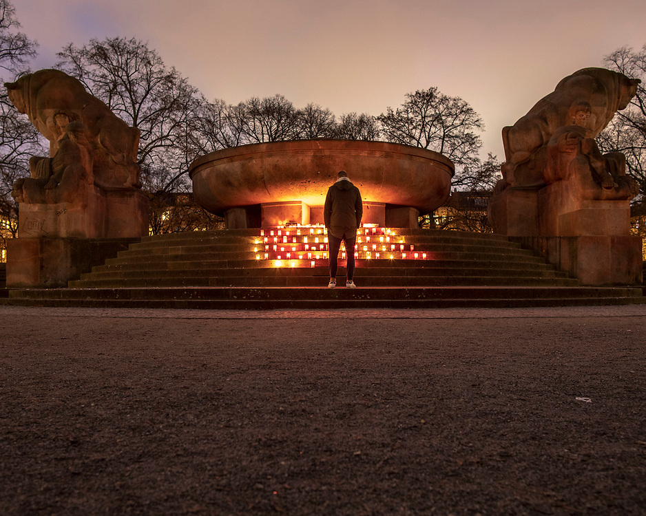 "A person watches candles at  a makeshift memorial in Berlin, Germany, January 17,  2021. The memorial is part of the initiative  ""Corona-Tote sichtbar machen"" (lit. Make corona deaths visible) by Christian Y. Schmidt and Veronika Radulovic,  since December 6, 2020, people gather at the fountain of Arnswalder Platz every Sunday at 16:00, light candles and place placards with the current death toll reported in Germany at the time. The death toll in Germany by variouse sources revolved around 47,000."