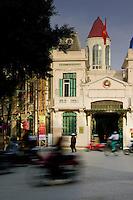 Motorbikes whizz by police station near Hoan Kiem Lake in Hanoi.