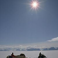 Eclipse Sound, north of Baffin Island, Canada.A tourist in a komatik sled behind a snowmobile on the frozen ocean.