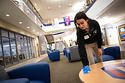 Student employee Taylor (CQ), wipes down a table with a cleaning wipe in the Lincoln Park Student Center during the COVID-19 (coronavirus) pandemic the week of March 16, 2020. During finals week of the winter quarter and into the spring quarter of 2020, DePaul instituted practices of social distancing, online classes and teleworking for all faculty, staff and students. (DePaul University/Jeff Carrion)