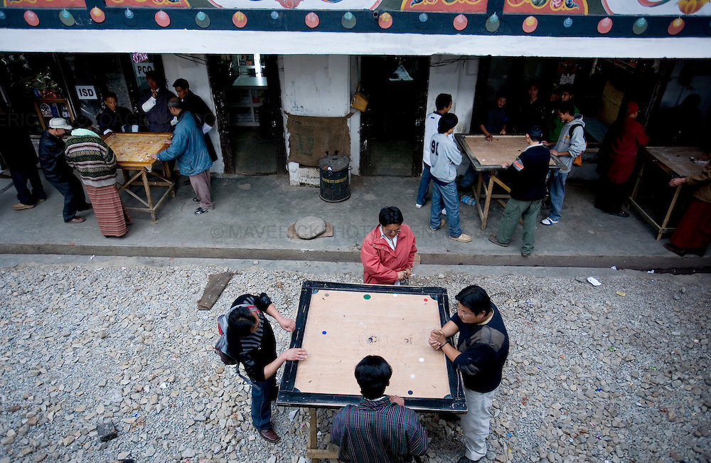 Men playing carom on the streets of Thimpu.  Commonly described as the last Himalayan Shangrila, Bhutan is a country of unique serenity, harmony, and beauty. Nestled between India, China, and Tibet, this independent country whose name translates as 'the Land of the Thunder Dragon' has for the past 300 years  proactively followed a policy of isolation and cultural protection. Travel in and out of the country is strictly regulated, and the impact of outside influences on the local culture is carefully monitored. Spirituality is an important aspect of Bhutanese culture, with Buddhism being interlinked with everyday life. Gross National Happiness (GNH), as opposed to GNP/GDP, forms the cornerstone of its development strategy which focuses on a holistic development strategy that complements its cultural and Buddhist spiritual values.