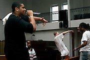 Michael, 17, (left) and Tykym, 18, (centre), members of the Hells Most Wanted, a Hip Hop Christian group, singing lyrics for the dancing devotees during a Mass Service at the Hip Hop Church in Harlem, New York, NY., on Thursday, June 22, 2006.  A new growing phenomenon in the United States, and in particular in its most multiethnic city, New York, the Hip Hop Church is the meeting point between Hip Hop and Christianity, a place where ëGodí is worshipped not according to religious dogmatisms and rules, but where the ëHoly Spirití is celebrated by the community through young, unique, passionate Hip Hop lyrics. Its mission is to present the Christian Gospel in a setting that appeals to both, those individuals who are confessed Christians, as well as those who are not regularly attending traditional Services, while helping many youngsters from underprivileged neighbourhoods to feel part of a community, to make them feel loved and to help them not to give up when problems arise. The Hip Hop Church is not only forward-thinking but it also has an important impact where life at times can be difficult and deceiving, and where young people can be easily influenced for the worst purposes. At the Hip Hop Church, members are encouraged to sing, dance and express themselves in any way that the ëSpirit of Godí moves them. Honours to students who have overcome adversity, community leaders, church leaders and some of the unsung pioneers of Hip Hop are common at this Church. Here, Hip Hop is the culture, while Jesus is the centre. Services are being mainly in Harlem, where many African Americans live; although the Hip Hop Church is not exclusive and people from any ethnic group are happily accepted and involved with as much enthusiasm. Rev. Ferguson, one of its pioneer founders, has developed ëHip-Hop Homileticsí, a preaching and worship technique designed to reach the children in their language and highlight their sensibilities, while bringing forth Christianity. This ëKeep It Realí