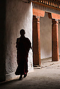 BHUTAN, WANGDUE PHODRANG DZONG (A dzong is a fortress and seat of civil and religious power -- Buddhism). A monk is walking past  a white wall in silhoutte. There are two pilars in the background.