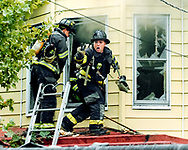 A Trenton firefighter (Gary Szabo) signals to other firefighters on the ground that two people, whom later die, are trapped inside the burning house on Walnut Ave. in Trenton, New Jersey.<br /> 10/21/04