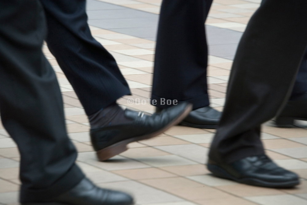businesspeople legs and feet all walking in the same direction