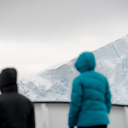 "Two passengers stand on the deck of a ship passing through the beautiful Lemaire Channel on the western side of the Antarctic Peninsula. The Lemaire Channel is sometimes referred to as ""Kodak Gap"" in a nod to its famously scenic views."