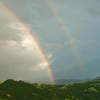A double rainbow arcs over the Story Hills near Bozeman, Montana.