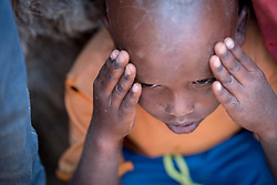 27 January 2019, Burka Dare IDP site, near Micha, Seweyna woreda, Bale Zone, Oromia, Ethiopia: A boy puts his hands to his head in the Burka Dare site for internally displaced people. The Lutheran World Federation supports internally displaced people in several regions of Ethiopia, through emergency response on water, sanitation and hygiene (WASH) as well as long-term development and empowerment projects, to help build resilience and adapt communities' lifestyles to a changing climate.
