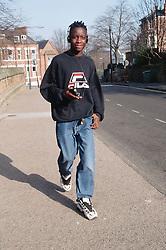 Teenage boy walking along street listening to walkman,