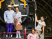 25 JUNE 2016 - BANGKOK, THAILAND:  State Railways of Thailand employees in traditional clothing on the front of a historic steam engine in Hua Lamphong train station. Hua Lamphong train station opened on June 25, 1916 after six years' construction. The station was built in an Italian Neo-Renaissance-style, with decorated wooden roofs and stained glass windows. The architecture is attributed to Turin-born Mario Tamagno. There are 14 platforms, 26 ticket booths, and two electric display boards. Hua Lamphong serves over 130 trains and approximately 60,000 passengers each day. Since 2004 the station has been connected by an underground passage to the MRT (Metropolitan Rapid Transit) subway system's Hua Lamphong Station.     PHOTO BY JACK KURTZ
