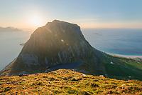 Autumn sun shines from behind Veggen mountain peak, Vestvågøy, Lofoten Islands, Norway