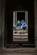 Four tour guides in blue uniform sit having a break outside a temple in Angkor Thom, Siem Reap Province, Cambodia, South East Asia. <br /> (photo by Andrew Aitchison / In pictures via Getty Images)