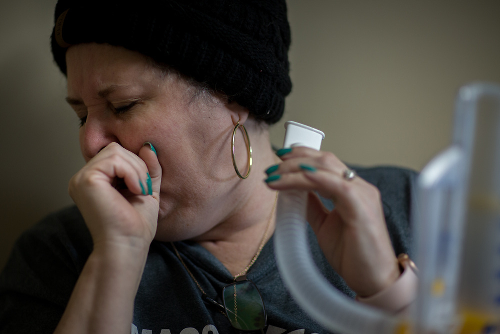 ALMA, GA - MARCH 30, 2021: Martin coughs after taking a pulmonary function test with an incentive spirometer. The device measures volume of air she can inhale. Lack of lung capacity is often a problem with CoVid patients who have spent weeks on a ventilator. (AJC Photo/Stephen B. Morton)