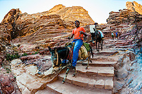 Bedouin men on donkeys, descending the 800 steps that lead to The Monastery monument, Petra Archaeological Park (a UNESCO World Heritage Site), Petra, Jordan.
