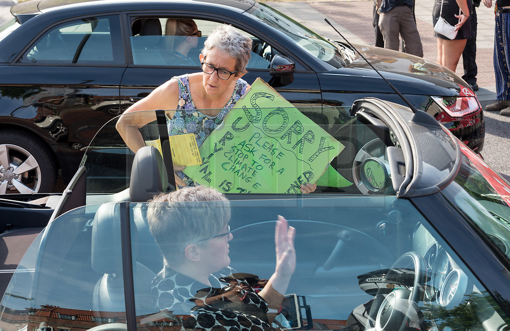 """© Licensed to London News Pictures. 17/07/2019; Bristol, UK. Extinction Rebellion Summer Uprising 2019. A """"De-escalation"""" member speaks to motorists stuck in traffic blocked by Extinction Rebellion to explain the reasons for the action. Extinction Rebellion block a major road junction at morning rush hour on Newfoundland Road coming into Bristol city centre causing traffic delays up the M32 to the M4 motorway. Campaigners locked themselves onto a pink bath tub, and held 7 minute roadblocks on other parts of the junction complex. Extinction Rebellion are holding a five-day 'occupation' of Bristol, by occupying Bristol Bridge in the city centre and traffic has to be diverted and carrying out other events. As part of a country-wide rebellion called Summer Uprising, followers will be holding protests in five cities across the UK including Bristol on the theme of water and rising sea levels, which is the group's focus for the South West. The campaign wants the Government to change its recently-set target for zero carbon emissions from 2050 to 2025. Photo credit: Simon Chapman/LNP."""