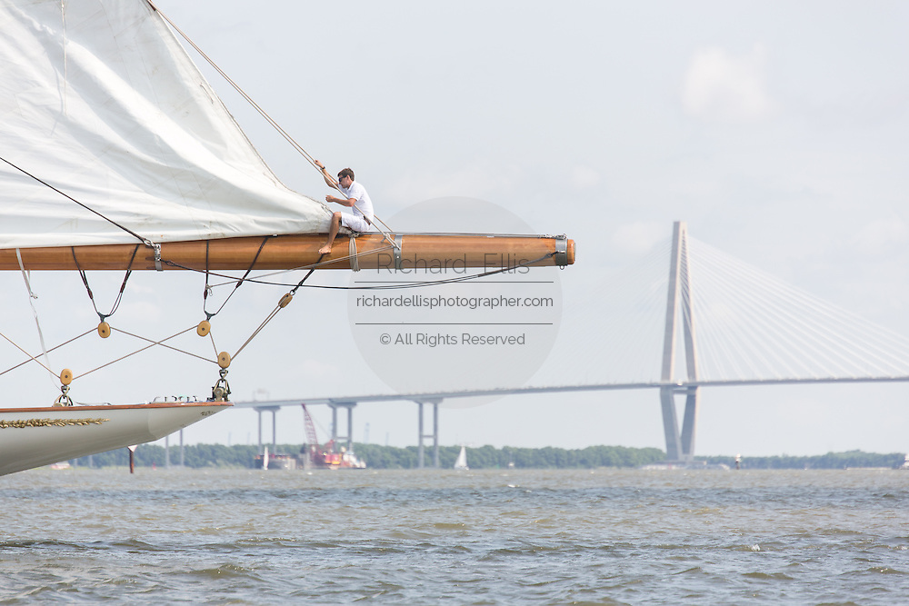 A deck hand rigs the sails on the 196-foot sailing yacht Germania Nova as it sails Charleston Harbor with the Arthur Ravenel Jr. Bridge in the background June 26, 2013 in Charleston, South Carolina.