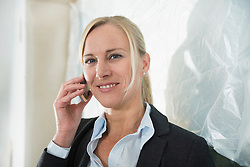 Female architect telephoning at construction site of new building