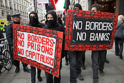 London, UK. Tuesday 11th June 2013. Anti capitalist protesters demonstrate holding placards against the upcoming G8 summit in central London, UK.