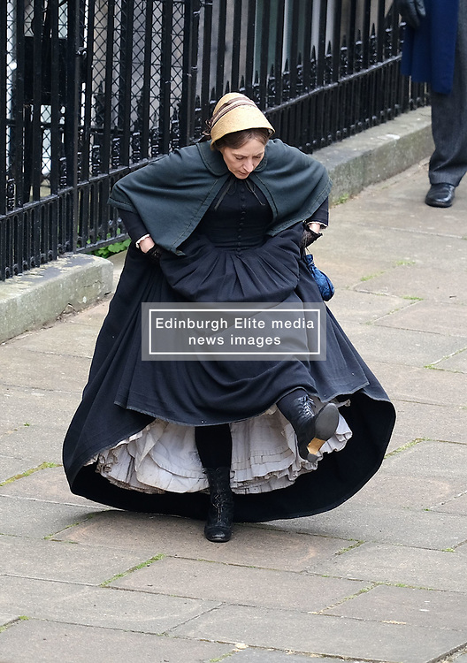 """Moray Place in Edinburgh's Georgian old town was turned into 19th century London for Julian Fellowes' new ITV show """"Belgravia"""".<br /> <br /> Pictured: An actress dressed as a maid checks her boots are laced up correctly but has to make some adjustments before she runs along the street.<br /> <br /> Alex Todd 