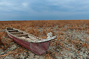 A traditional Marsh Arab boat sits on the cracked and dry earth of the Central Marshes of Southern Iraq. Considered by many as the location of the Biblical Garden of Eden, the marshes once covered more than 15,000 Sq Kms. During the 1990s Shia insurgency Saddam Hussein drained and poisoned the marshes driving most of the population into the already overcrowded cities.
