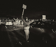 People protest and stop traffic along an Emeryville highway.