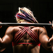 Female athlete lifting weights and preparing to squat.