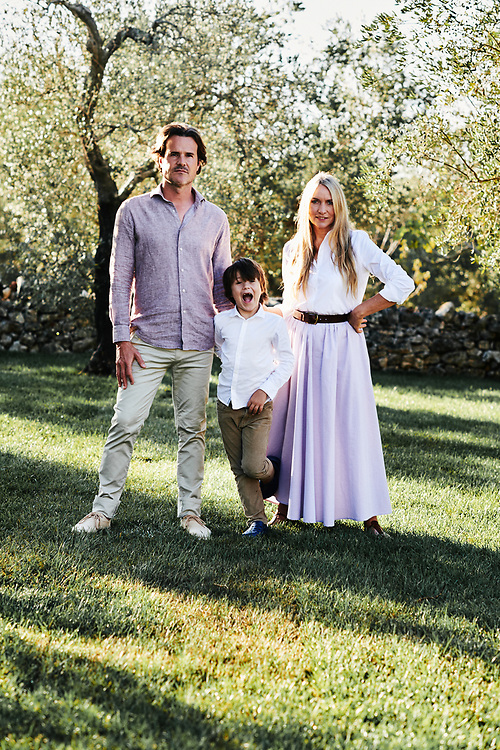 Collette Dinnigan, her husand Bradley Cocks and their son Hunder posing in their villa's garden. Ostuni, Italia. September 28, 2019.