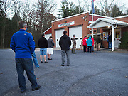 Early morning voters wait in an ever growing line to cast their ballots on Election Day. Early morning voters enter the polling station one-by-one to ensure safe distancing.