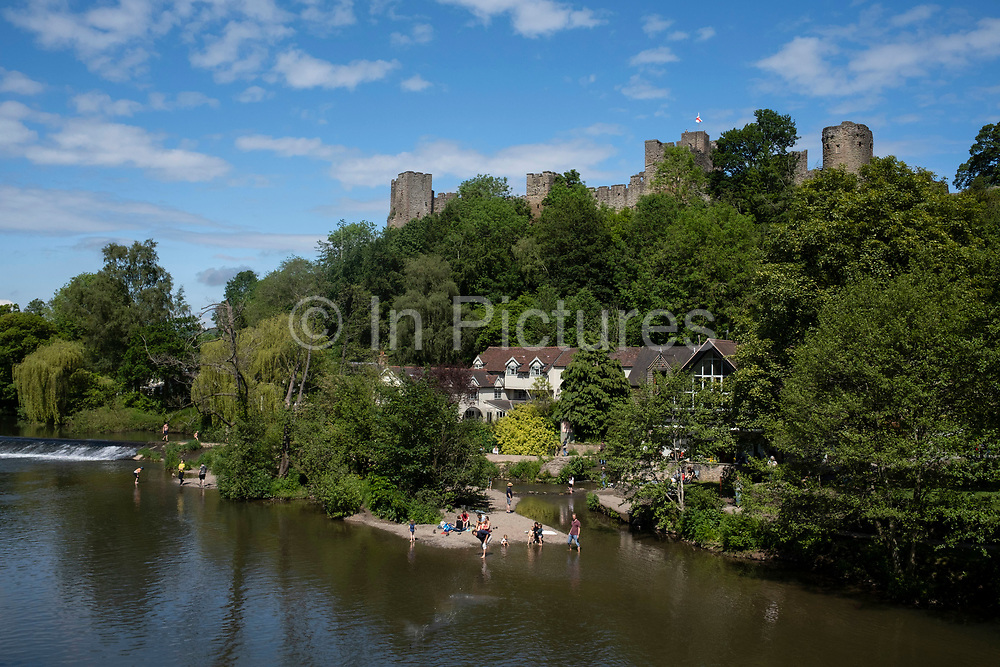 View over the River Teme as bathers enjoy swimming, paddling and playing in the river water near the weir looking towards towards Ludlow Castle on 6th June 2021 in Ludlow, United Kingdom. Ludlow is a market town in Shropshire, England. With a population of approximately 11,000, Ludlow is the largest town in south Shropshire. The town is near the confluence of two rivers. The oldest part is the medieval walled town, founded in the late 11th century after the Norman conquest of England. It is centred on a small hill which lies on the eastern bank of a bend of the River Teme. Atop this hill is Ludlow Castle and the parish church, St Laurences, the largest in the county. From there the streets slope downward to the River Teme.