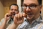 """Co-owners Perry Patten (left) and Scott Tripp show how safe the organic biscuits are, by sampling a """"Sunday Dinner"""" meat-flavored treat. They said for humans the biscuits come off as quite bland, because the human tongue doesn't have as many taste buds as a dog's. But dogs love them and gulp them down due to the meaty taste."""