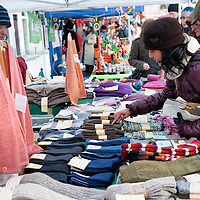 "VENICE, ITALY - DECEMBER 18:  A woman buys biological clothing at  ""l'Altro Natale"" Christmas market on December 18, 2010 in Venice, Italy. ""L'Altro Natale"" an alternative Christmas market organised over the busiest shopping week end of the year promotes fair trade and alternative commerce."