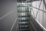 Employees of an auditing stride along high on top floor walkways at the company's London headquarters.