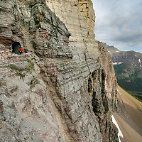 A six-foot backpacker shrinks before the heights of the entrance of the Ptarmigan Tunnel in Glacier National Park.