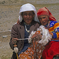 A nomadic Kyrgyz woman spins wool with her grand daughter near their summer hut in the Pamir Mountains of Xinjiang Province in far western China.