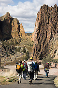 A group of rock climbers walk towards the cliffs of Smith Rock State Park, Oregon.