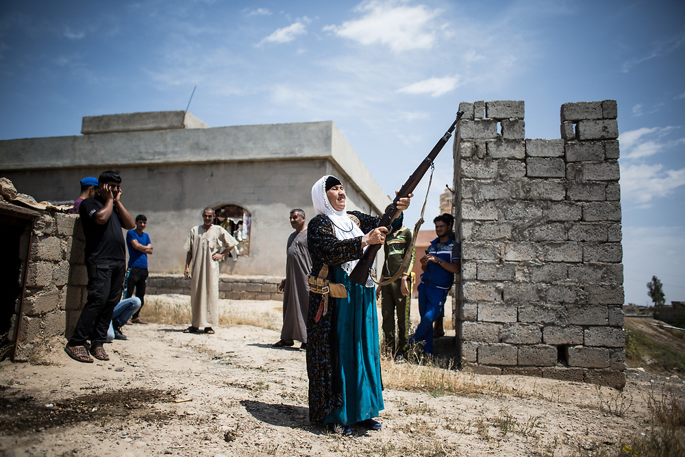 """An old female fighter, Nazha, fires a bullet at ISIS's position with a menacing look near Mosul. She is a 65-year-old woman who fights against ISIS in a small village near Mosul in Iraq. There are 40 families live in the village but they have only two rifles to protect themselves. ISIS is just 1km away from them and they always attack the village at night. They don't get any support from Iraqi police nor Iraqi army. She said """"we are afraid of ISIS but we have to fight to protect the people here."""" <br /> <br /> ナザ(65歳)はある小さな村に住む女性で、ISを相手に銃を手に取った。村には40家庭が住むが、自衛のための武器はライフル2丁だけで、ISとの距離はたった1km。彼らは夜になると攻撃を仕掛けてくるという。イラク政府や警察からの支援は何もない。ISは恐ろしいが、村の人たちを守るために戦うしかないと彼女は言った。2017年5月イラク撮影。"""