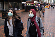People wearing face masks for protection against Coronavirus on 14th March 2020 in Birmingham, England, United Kingdom. Due to the rapidly spreading coronavirus outbreak a number of mainly Chinese / Asian people are wearing face masks in public. Coronavirus or Covid-19 is a new respiratory illness that has not previously been seen in humans. While much or Europe has been placed into lockdown, the UK government is due to announce more stringent rules as part of their long term strategy.