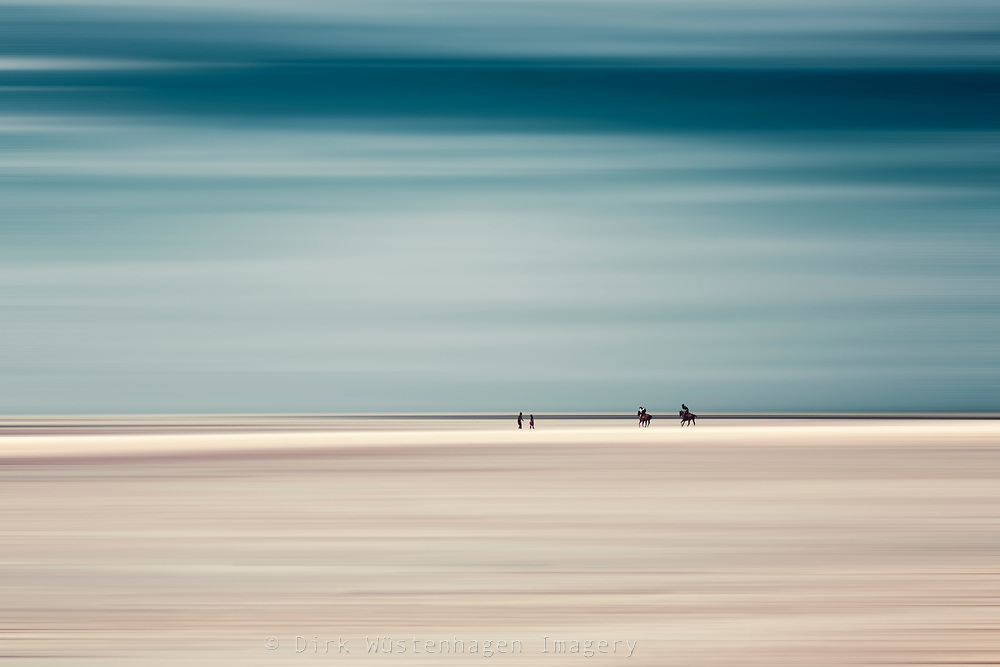 Riding horses on a beach - abstract photography