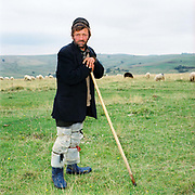 Portrait of a shepherd wearing plastic leggings and a traditional shepherd's hat in the Carpathian Mountains, Romania. Shepherd's hats are totally handmade. The interior should be white and it should hold water so that the shepherd can use it to collect water from streams to wash in when he's up in the mountains. Whereas in most countries sheep are reared for wool and meat, in Romania these are seen as by-products and the real purpose of the flock is to produce branza or cheese.