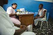 Keukeu Laito, 29, who is 5-month pregnant with her second child, meets with a midwife during a prenatal consultation at the Libreville health center in Man, Cote d'Ivoire on Wednesday July 24, 2013.