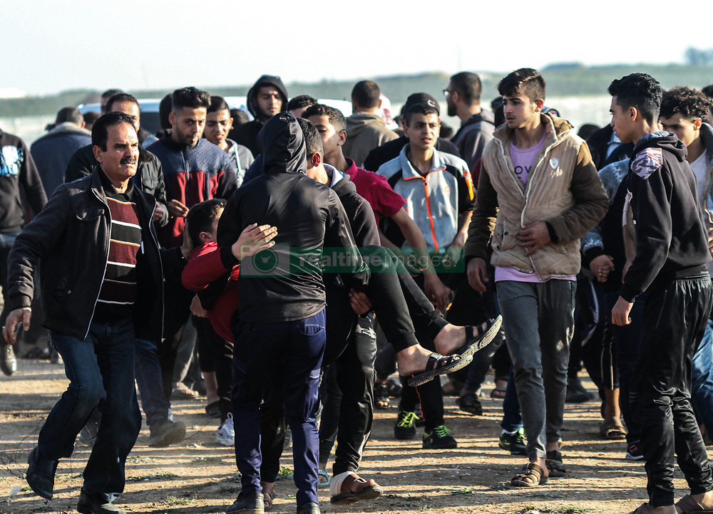 """March 22, 2019 - Gaza, 22th March 2019. A number of Palestinian demonstrators are injured in clashes with the Israeli army in the Malika district on the east of Gaza City during this Friday 51st Great March of Return rally. Thousands of demonstrators had gathered at several points on the Gaza-Israeli borders with some hurling rocks and burning tires, and with Israeli troops firing live ammunition, rubber-coated steel bullets, and tear gas at protesters. According to the Gaza Health Ministry, 30 Palestinians were shot and injured by Israeli live fire, while dozens of others suffered from tear-gas inhalation. The Israeli military stated that troops had responded with """"riot dispersal means"""" and fired in accordance to standard operating procedures. ''The Great March of Return'' protests began on March 30th last year with thousands of Gazans demonstrating at least weekly in an attempt to break the ongoing Israeli siege on Gaza and to demand the right of Palestinian refugees to return to their original homeland, now in present-day Israel. Since the protests started, 260 Palestinians have been killed and 29,000 others wounded by the Israeli army (Credit Image: © Ahmad Hasaballah/IMAGESLIVE via ZUMA Wire)"""