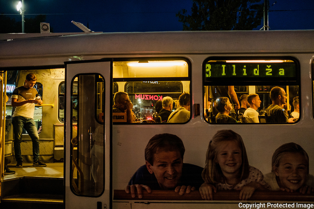 As evening sets a young man looks at his  phone onboard the city tram. Even though it has been 25 years since the Siege of Sarajevo began all young people are fully aware of what happened even if it was before their time.