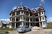Wealthy Roma Gypsy homes. Extravagant houses in garish colours, in typical Romanian Gypsy style with ornate metal zinc roofs and several balconies, often with symbols such as Mercedes Benz emblems, which was once considered the best made car. These houses or palaces often take years to build, their occupants working abroad, finishing the structures little by little. Huedin, near Cluj-Napoca, Romania