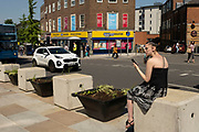 Street scene of a young woman sitting on Trinity Street in the UK City of Culture 2021 on 23rd June 2021 in Coventry, United Kingdom. The UK City of Culture is a designation given to a city in the United Kingdom for a period of one year. The aim of the initiative, which is administered by the Department for Digital, Culture, Media and Sport. Coventry is a city which is under a large scale and current regeneration.