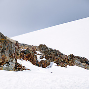 Jagged exposed rocks stick out from the deep snow on Petermann Island, Antarctica.