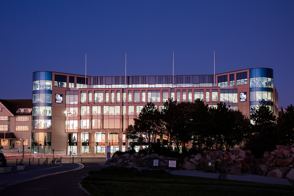 Corporate offices lit up at night in the offshore banking and finance district of St Helier, Jersey, CI