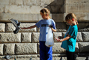 Two children (9 years old, 5 years old), feeding pigeons, Dubrovnik old town, Croatia